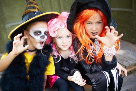 Portrait of three Halloween girls looking at camera with frightening gesture photo