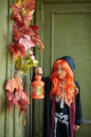 antichrist: Portrait of Halloween girl with lantern standing by the door of dilapidated house