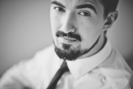 facial: Black-and-white image of posh guy looking at camera