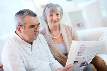 Portrait of mature man reading newspaper at home with his wife near by Stock Photo - 22247085