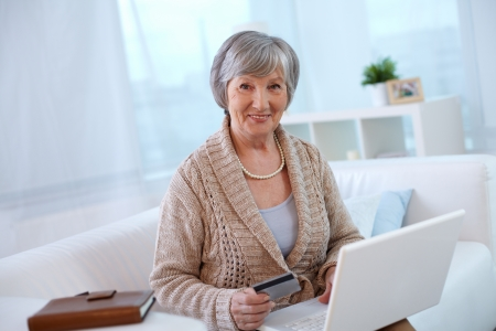 Portrait of aged female with laptop looking at camera Stock Photo