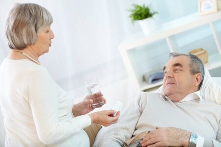Portrait of mature woman giving tablets to her sick husband at home Stock Photo - 22247234
