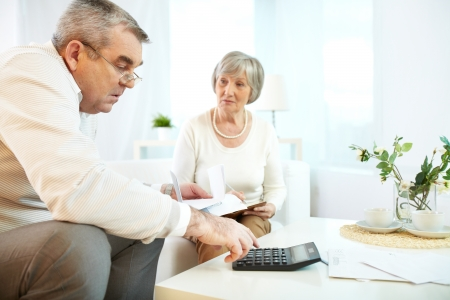 Portrait of mature man and his wife making financial revision at home Stock Photo - 22247351