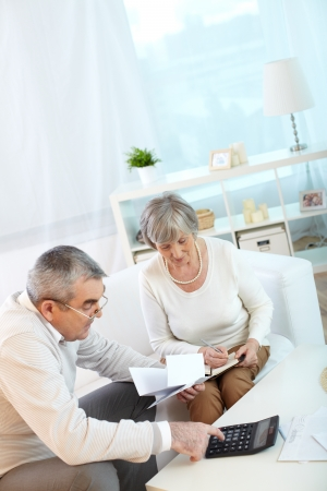 retirement  age: Portrait of mature husband and wife making financial revision at home