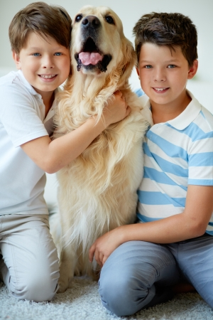 Portrait of happy siblings with their pet looking at camera at home photo