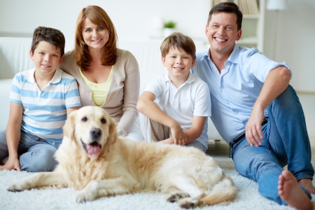 Portrait of happy family with their pet having rest at home photo