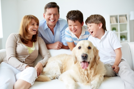 Portrait of happy family with their pet having good time at home photo