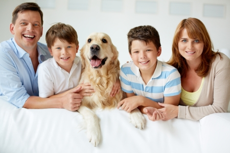 Portrait of happy family with their pet looking at camera