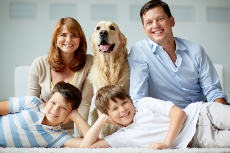 Portrait of happy family with fluffy Labrador resting at home photo
