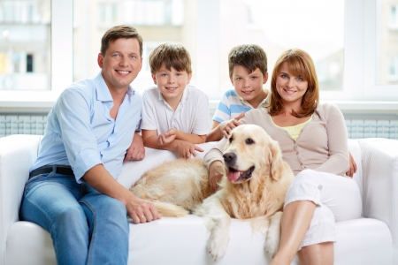 look inside: Portrait of happy family with their pet having rest at home