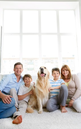 Cheerful family with their pet sitting on the floor at home photo