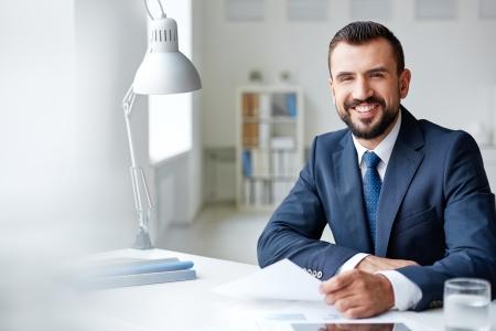 Lachend zakenman in pak kijken camera in het kantoor
