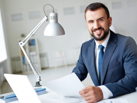 Smiling businessman in suit looking at camera while working in office photo