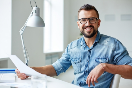 Glimlachende zakenman in denim shirt en bril kijken camera in het kantoor Stockfoto
