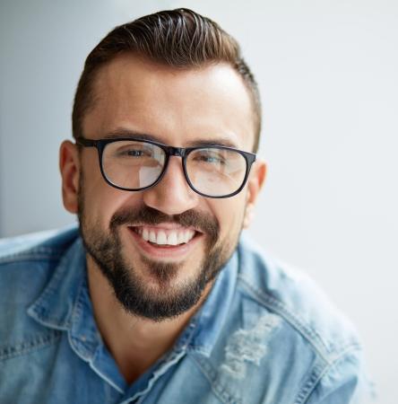 bigote: Hombre feliz en camisa de mezclilla y lentes que miran a la c�mara con una sonrisa con dientes Foto de archivo