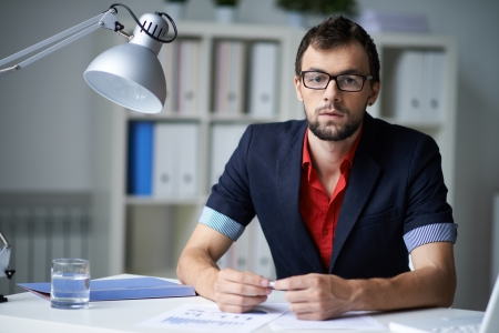 casual office: Handsome businessman in smart casual and eyeglasses looking at camera in office Stock Photo