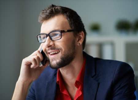 busy beard: Handsome businessman in smart casual and eyeglasses speaking on the phone