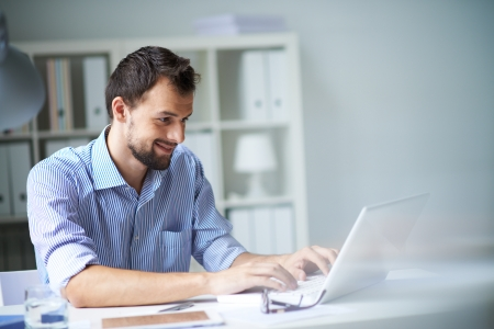 guy with laptop: Handsome businessman working with laptop in office Stock Photo