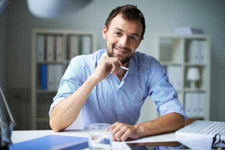 attractive office: Smart businessman looking at camera with smile in office