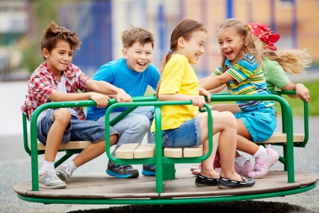 playground ride: Image of joyful friends having fun on carousel outdoors  Stock Photo