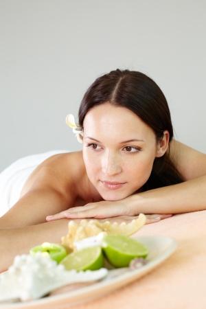 therapeutical: Pretty brunette lying in spa salon