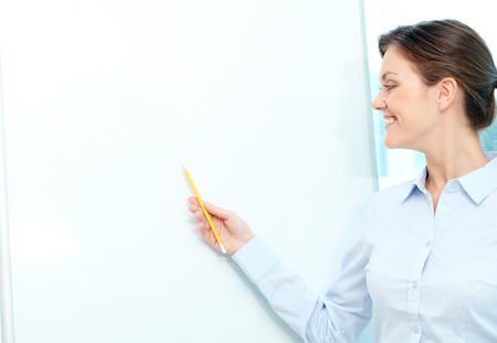 lecturing: Portrait of a smiling teacher pointing at a blank whiteboard Stock Photo