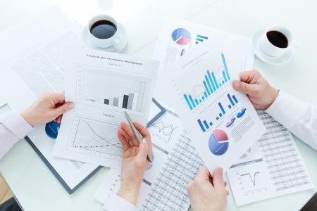 businesspartners: Por encima de ?ngulo de maduras manos businesspartners durante la discusi?n de los documentos