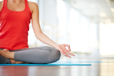 meditation woman: Lower part of slim female meditating in pose of lotus in gym