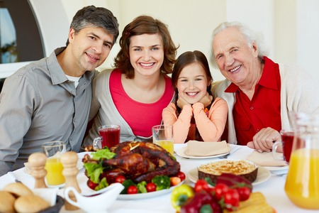 Portrait of happy family sitting at festive table and looking at camera photo