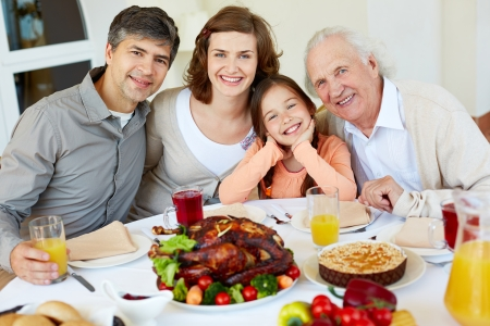 family dinner: Portrait of happy family sitting at festive table and looking at camera Stock Photo