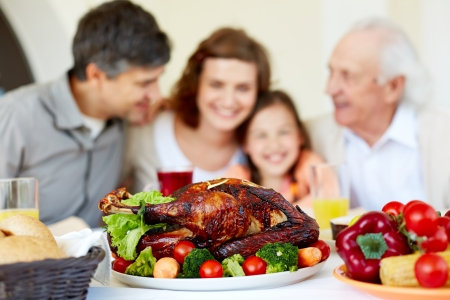 Image of roasted turkey on holiday table and family on background photo