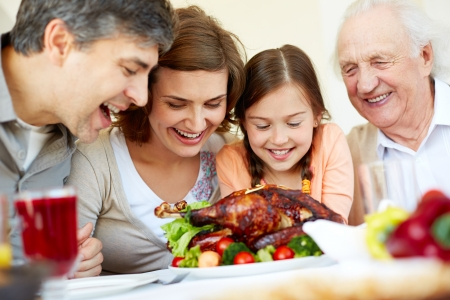 thanksgiving adult: Portrait of happy family sitting at festive table and looking at roasted turkey Stock Photo