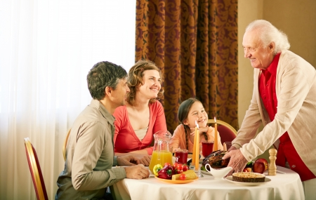 thanksgiving adult: Portrait of happy family sitting at festive table and looking at senior man during Thanksgiving dinner