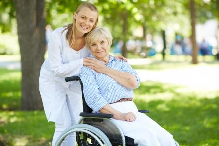 Mooie verpleegster en senior patiënt in een rolstoel zoekt op camera buiten