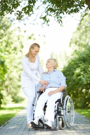 elderly care: Pretty nurse walking with senior patient in a wheelchair in park Stock Photo