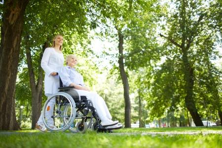 Pretty nurse walking with senior patient in a wheelchair in park photo