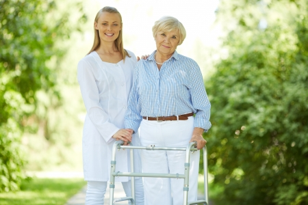 walker: Pretty nurse and senior patient with walking frame looking at camera outside Stock Photo
