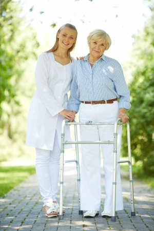 Pretty nurse and senior patient with walking frame looking at camera outside photo