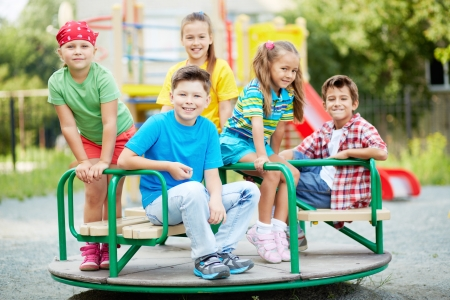 playground ride: Image of cute friends having fun on carousel outdoors