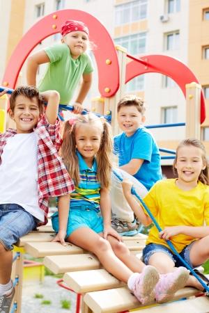 niños en area de juegos: Imagen de amigos alegres que se divierten en parque infantil al aire libre Foto de archivo