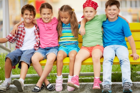 child: Happy friends looking at camera while sitting on bench outdoors  Stock Photo