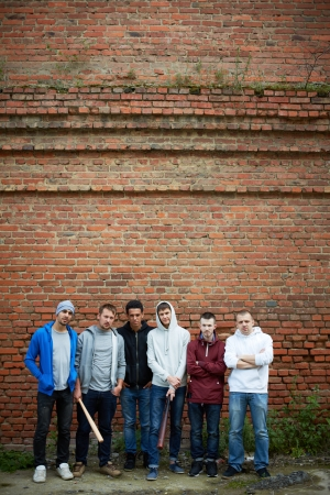 insurrection: Portrait of several street hooligans or rappers standing against brick wall