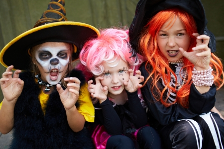 cute halloween: Portrait of three Halloween girls looking at camera with frightening gesture