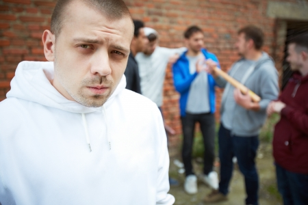insurrection: Portrait of angry guy looking at camera with his friends on background