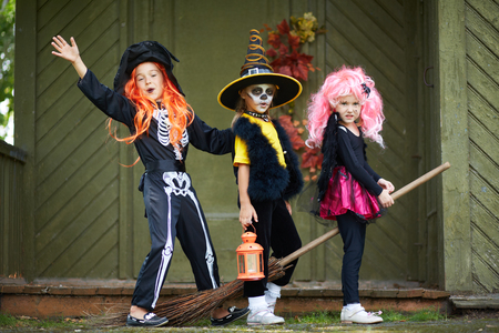 antichrist: Portrait of three Halloween girls with broom looking at camera outside