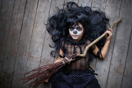 antichrist: Portrait of cute girl in black wig holding broom and looking at camera Stock Photo