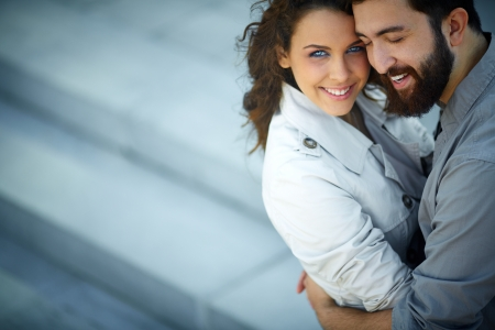 Image of happy woman looking at camera while being embraced by her sweetheart photo