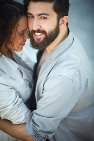 Image of happy man looking at camera while embracing his sweetheart photo