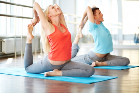 activewear: Portrait of happy young woman and man doing stretching exercise in gym Stock Photo