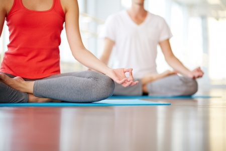 Lower part of slim female and man on back meditating in pose of lotus in gym photo